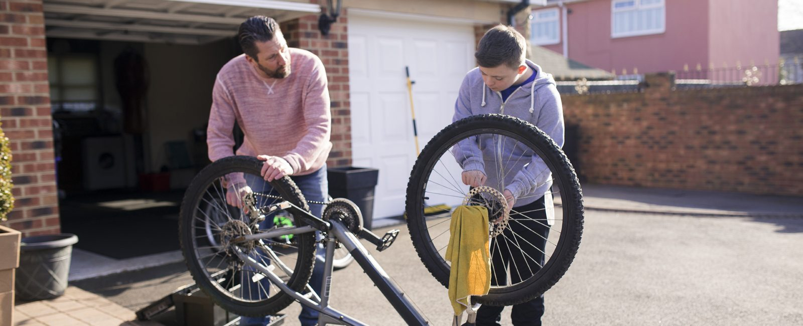 Stock father son fixing bike